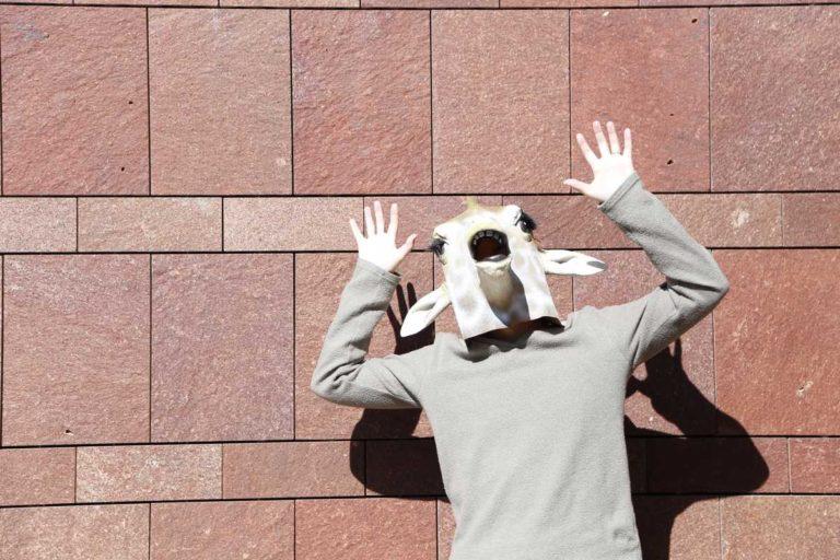 驚いているキリンのマスクを被った人