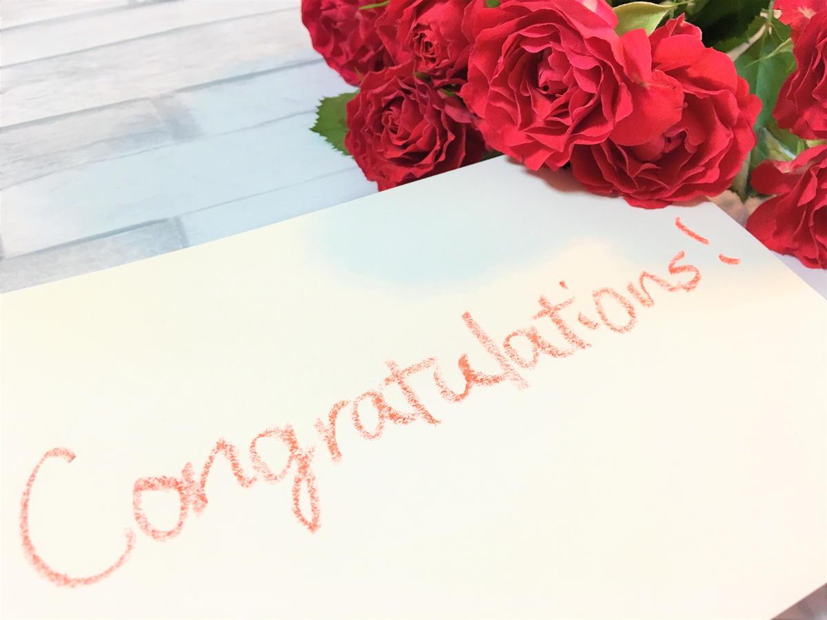 英文の書かれた紙とバラの花